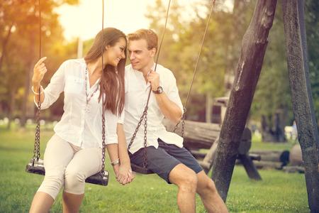 columpios: Pareja amorosa en cita romántica en los columpios al aire libre Foto de archivo