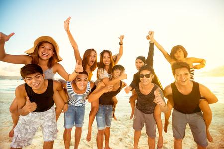 Parejas felices en chicos de la playa que llevan las niñas en cuestas, se divierten Foto de archivo - 42200251