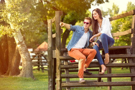 couple relaxing: Modern fashion couple of young lovers in the park