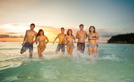 amistad: j�venes felices jugando en el mar, un grupo de amigos que se divierten Foto de archivo