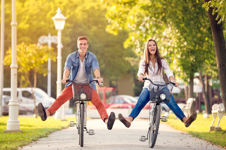 Happy funny young couple riding on bicycle Imagens