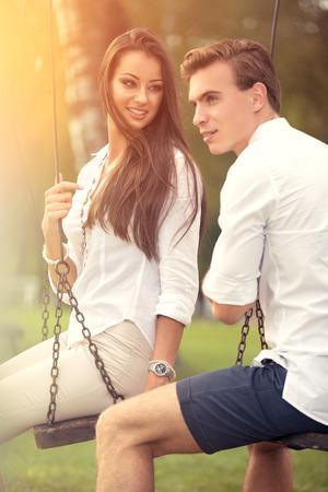 girl on swing: Love couple on swings at park