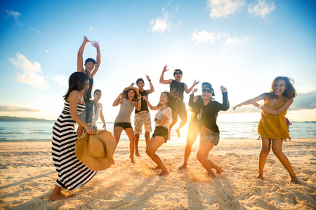 10: Happy young people on beach Stock Photo