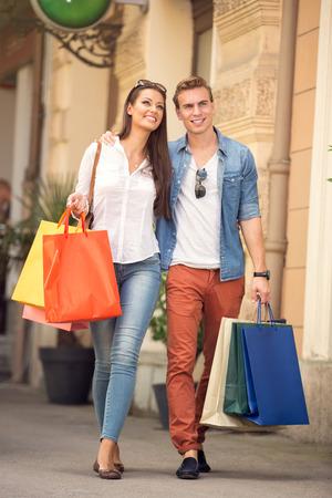 Junge Paar zu Fuß mit Einkaufstüten Standard-Bild - 42200934
