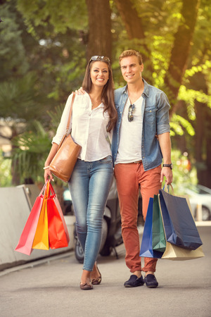 sidewalk sale: shopping couple with shopping bags walking Stock Photo