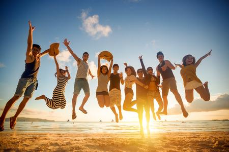 生活方式: 年輕人跳躍在海灘集團