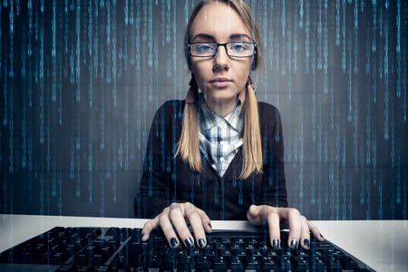 Nerd girl utilisant un ordinateur par un code binaire sur l'écran Banque d'images