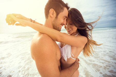 passionate embrace: young happy couple with draw heart on tropical beach. Honeymoon