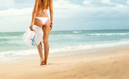 Fit woman standing on beach with hat in hand , back view