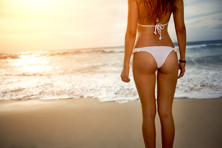 young bikini: Sexy back of a beautiful woman in bikini on sea background. Sexy buttocks Stock Photo