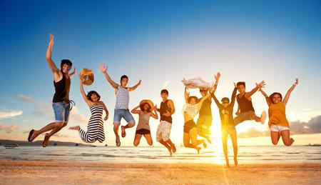 brincando: Grupo de amigos que saltan en la playa, concepto de diversión salto Foto de archivo