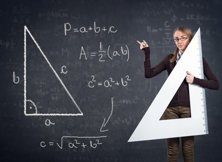 female student with a big ruler pointing at  Pythagorean theorem on blackboard Stock Photo