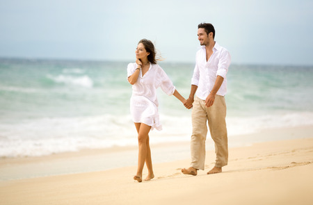 Young happy couple walking on beach and holding hands