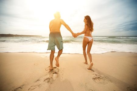 pareja apasionada: Pares del amor en la playa con coraz�n de dibujo en la arena