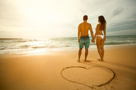 Promenade sur la plage d'aimer couple avec forme de coeur sur le sable.