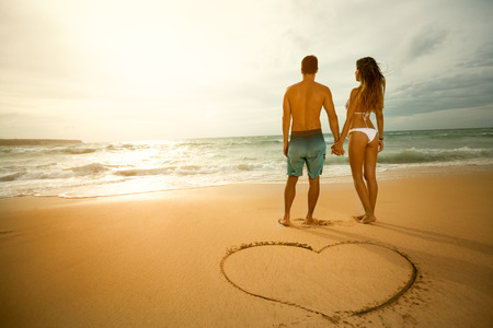 Walk on the beach of loving couple with heart shape on the sand.