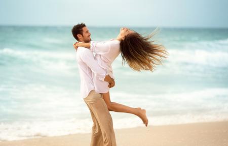 Jong koppel samen te genieten op het strand, jonge man spinnen zijn meisje in een cirkel Stockfoto