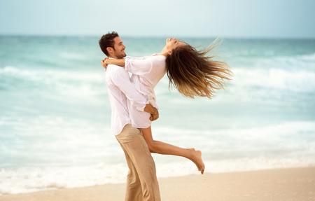 Young couple enjoying together on beach, young man spinning his girl in a circle