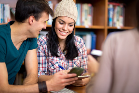 studding: Couple of beautiful young classmates having fun on cell phone after class Stock Photo