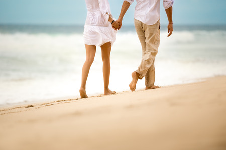 seaside: Barefoot couple walking on sandy beach