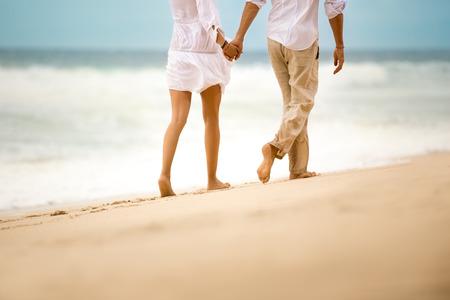 tomados de la mano: Pareja caminar descalzo en la playa arenosa