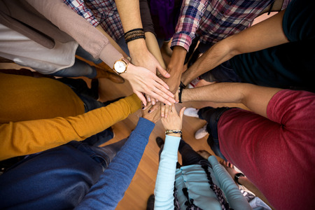 diverse hands: Unit and concord in multiethnic team, all hands together Stock Photo