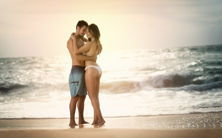 Young beautiful couple in love staying and kissing on the beach on sunset