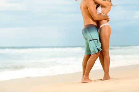 vacation: Attractive couple in embrace on sandy beach