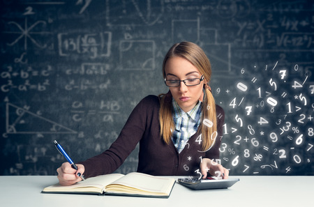 Schoolgirl doing  mathematics with math formulas