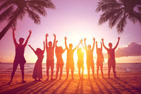Mensen springen op het strand, silhouet van vrienden tijdens zonsondergang tijd