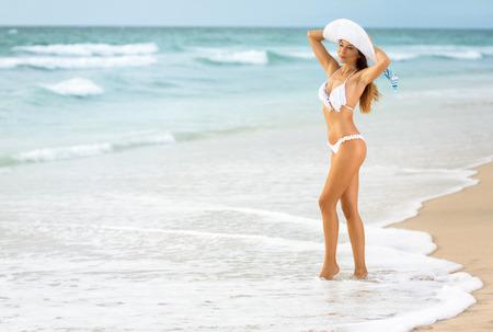 niñas en bikini: Joven mujer sexy en bikini blanco de pie en las olas en la playa