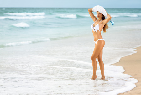 pink bikini: Young sexy woman in white bikini standing in waves on beach