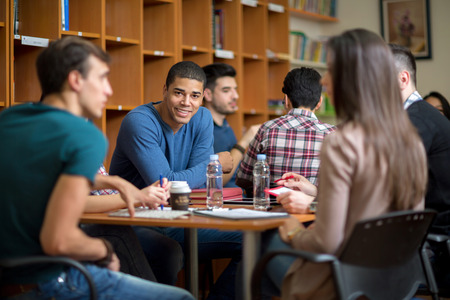 college: Young Latino American student socialize with friends after class in library