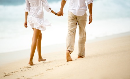 cogidos de la mano: Vista posterior de una pareja dando un paseo de la mano en la playa
