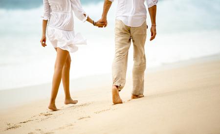 romance: Vista traseira de um casal tendo um passeio de mãos dadas na praia