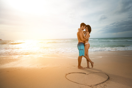 pareja abrazada: Joven pareja de enamorados, hombres y mujeres atractivas que disfrutan de cita rom�ntica en la playa al atardecer.