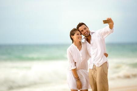 parejas romanticas: feliz pareja romántica en la playa tomar de la foto de sí mismos con el teléfono elegante Foto de archivo