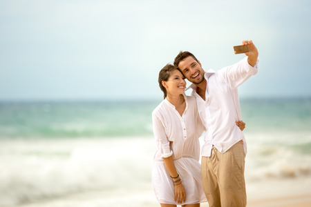 romantic beach: Happy romantic couple on the beach taking photo of themselves with smart phone