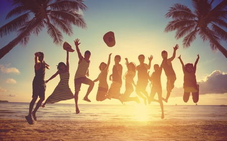 Groupe d'amis sautant contre le coucher du soleil