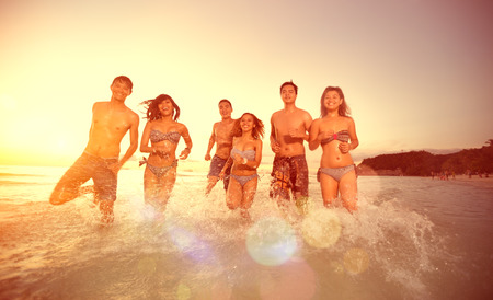 ocean water: Friends running into the sea, group of happy people having fun Stock Photo