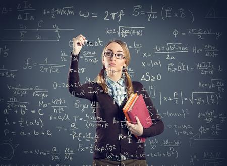 Criture de Student girl formules sur la transparence de paroi avant son Banque d'images - 43804406