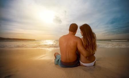 Couple romantique emplacement sur la plage et le coucher du soleil à la recherche Banque d'images