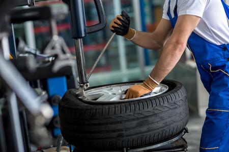 llantas: ingeniero equilibrar la rueda de coche en la equilibradora en el taller