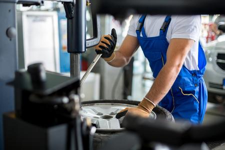 herramientas de mecánica: reparador mecánico reemplazar neumático en la rueda en el taller