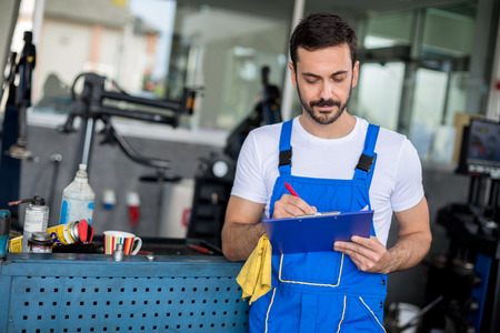 car repair: Mechanic in auto repair shop standing and writing on clipboard Stock Photo