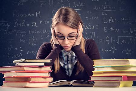 Jonge student met wanhopige uitdrukking zittend aan een bureau en op zoek naar haar boeken Stockfoto