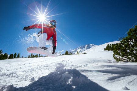 snowboard: Snowboarder taking a jump in fresh snow.