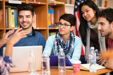 estudiantes: Grupo de estudiantes jóvenes que discuten sobre la tarea
