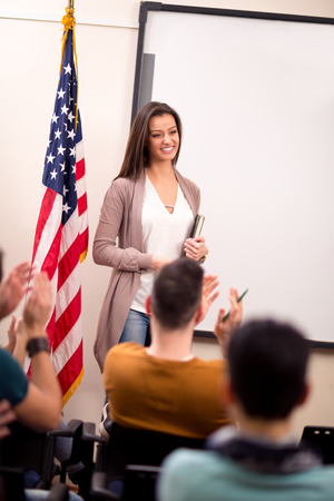clapping hands: Students clapping hands to young satisfied teacher Stock Photo