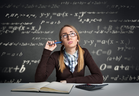 preoccupation: Young student with  thoughtful expression sitting at a desk with math formulas over her head